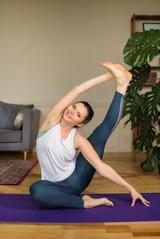 Bella atleta femminile esegue esercizi di stretching sulla stuoia in una stanza a casa