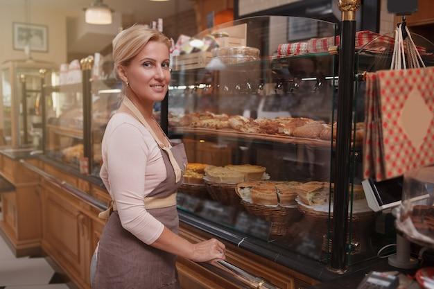 Bella donna baker vi dà il benvenuto nel suo negozio di panetteria, copia dello spazio