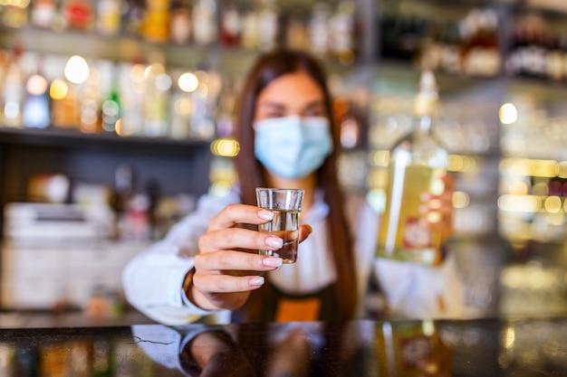 Bella donna barista con maschera protettiva che tiene un bicchierino con alcol durante la pandemia di coronavirus, scaffali pieni di bottiglie con alcol sullo sfondo