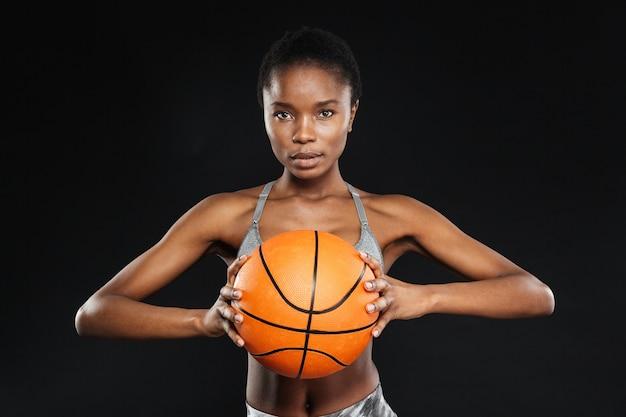 Bella giocatrice di basket isolata su un muro nero