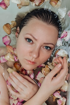 Bella femmina in bagno con petalo di rosa. mani nel telaio