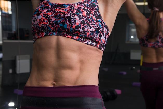 Muscoli addominali del bel corpo femminile in palestra con manubri.