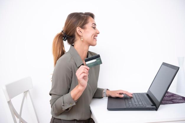 Bella femmina che acquista in linea usando il suo computer