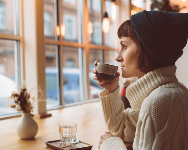 Bella femmina nella caffetteria nelle vacanze invernali di natale a luci di ghirlanda