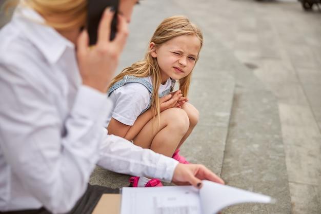 Bellissima bambina seduta sui gradini in città con sua madre che lavora sodo