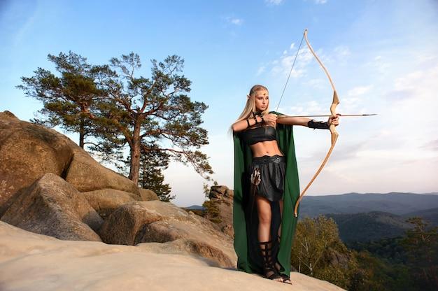 Bello arcere femminile dell'elfo nella caccia della foresta con un arco