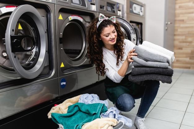 Bella dipendente femminile che lavora al negozio di lavanderia a gettoni.