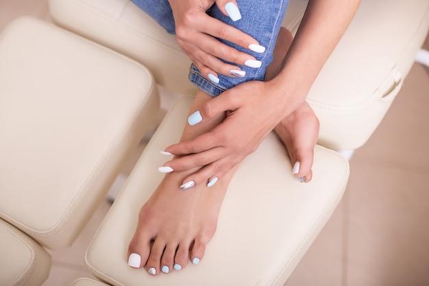 Bellissimi piedi e mani femminili con unghie alla moda per manicure e pedicure