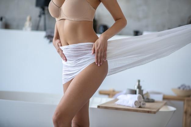 Bella figura femminile avvolta in tessuto bianco