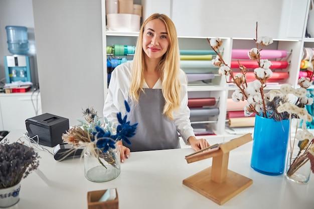 Bella fiorista femminile in posa nel suo studio di fiori