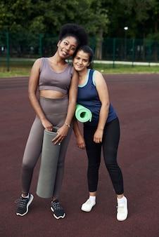 Belle amiche sono in piedi con tappeti sportivi in strada e si preparano per lo sport