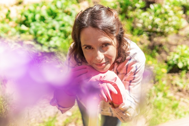 Bello giardiniere femminile con i fiori. una donna pianta piantine in un giardino di casa. il contadino tiene i germogli.
