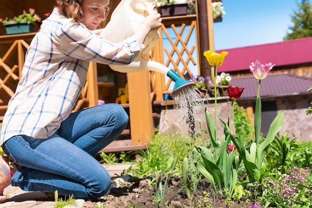 Bello giardiniere femminile con i fiori. una donna pianta piantine in un giardino di casa. il contadino sta innaffiando i letti.