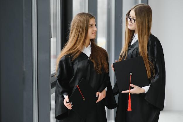 Bella donna laureata in piedi fuori da un gruppo di studenti