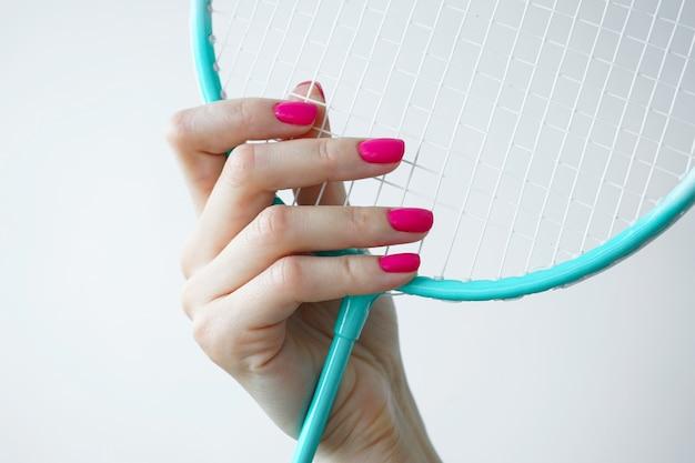 Bella mano femminile tiene una racchetta da badminton su uno sfondo bianco, close-up. bella manicure. concetto di sport e bellezza.