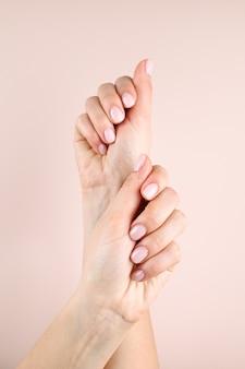 Belle mani femminili, su uno sfondo di colore beige