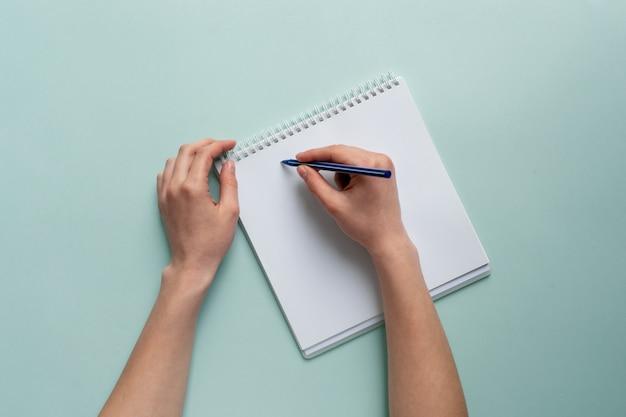 Le belle mani femminili tengono una matita sopra un taccuino. su uno sfondo blu, il concetto di creatività e disegno.