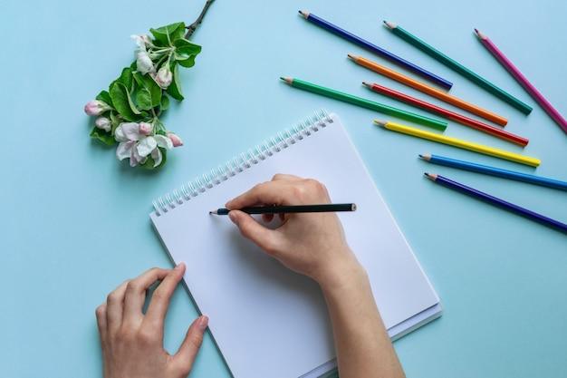 Le belle mani femminili tengono una matita sopra un taccuino sull'azzurro