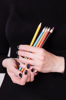 Belle mani femminili che tengono le matite colorate sul nero