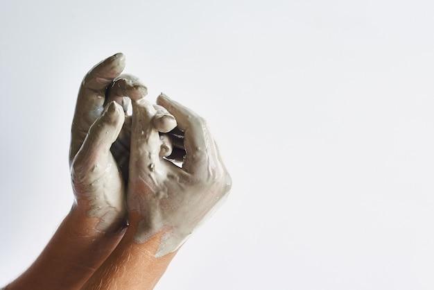 Belle mani femminili su uno sfondo chiaro spalmato di argilla grigia