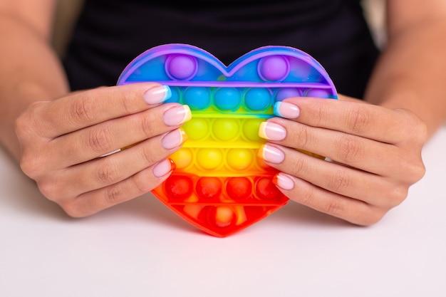 Belle mani femminili con unghie colorate per manicure che tengono un giocattolo pop it