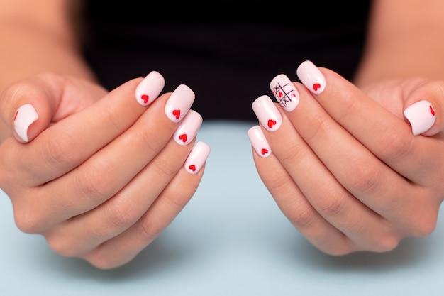 Belle mani femminili con un design creativo dei cuori di manicure