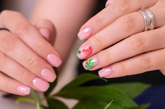 Belle mani femminili con unghie manicure creative, smalto gel nudo, design di foglie tropicali