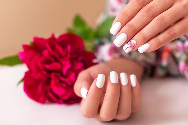 Belle mani femminili con manicure rosa, design di peonie
