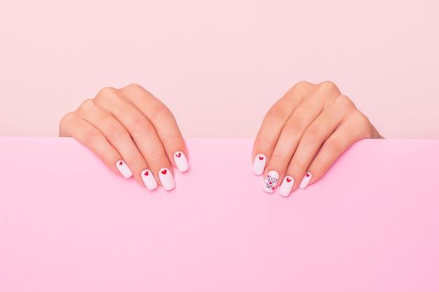 Belle mani femminili con il manicure bianco