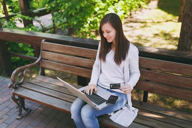 Bella carta di credito femminile della tenuta con lo spazio della copia. donna seduta su una panchina che lavora su computer pc portatile moderno, telefono cellulare in strada all'aperto sulla natura. ufficio mobile. concetto di business freelance.