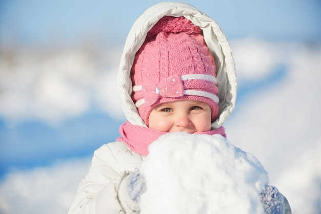Bella bambina indossa cappello rosa caldo e giacca con cappuccio, tiene enorme palla di neve, pone alla macchina fotografica con espressione allegra