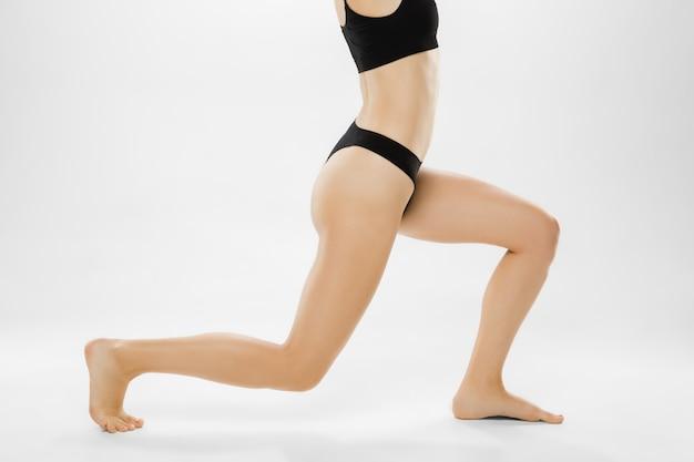 Belle gambe e pancia femminili isolate sulla depilazione della stazione termale dei cosmetici di bellezza del fondo bianco