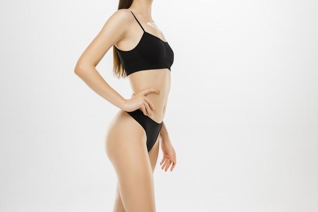 Belle gambe e pancia femminili isolate sulla parete bianca. corpo in forma e sportivo, sensuale con pelle ben curata in intimo.