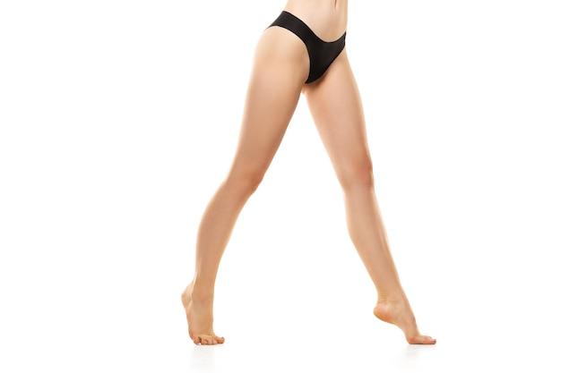 Belle gambe femminili, natiche e pancia isolate su bianco