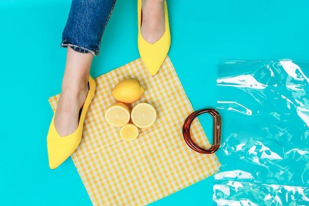Belle gambe femminili vestite con eleganti scarpe gialle senza tacco e borsetta con limoni luminosi. lay piatto