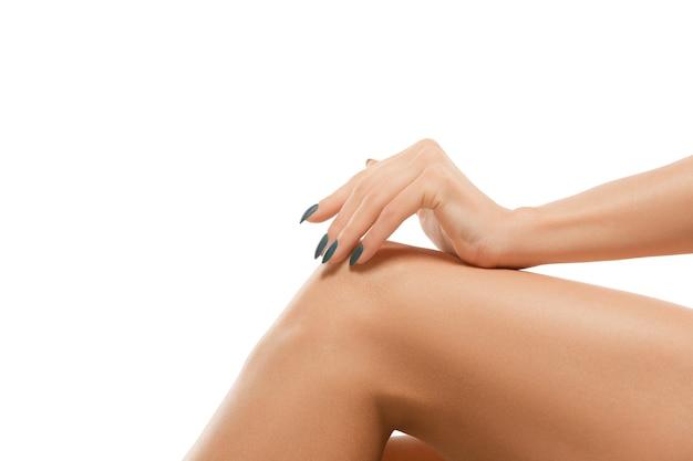 Belle gambe femminili e mano isolate sul muro bianco