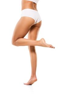 Belle gambe femminili isolate sulla parete bianca. concetto di bellezza, cosmetici, spa, depilazione, trattamento e fitness. corpo in forma e sportivo, sensuale con pelle ben curata in intimo.