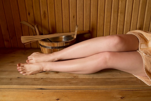 Bei piedini femminili nella sauna, accessori da bagno. secchio e bastoncini di legno