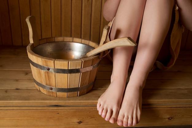 Bei piedini femminili nella sauna, accessori da bagno. secchio di legno