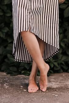 Bei piedini femminili in un primo piano del vestito corto. piedi nudi