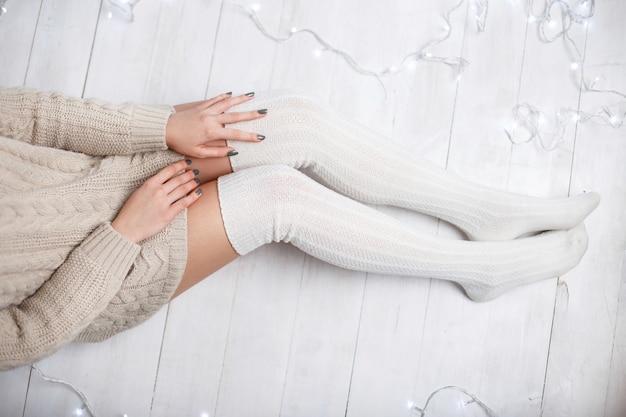 Bei piedini femminili in calzini lavorati a maglia bianchi su un pavimento di legno bianco