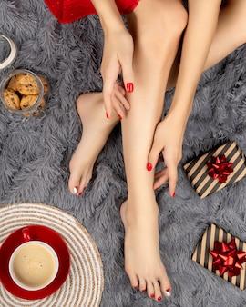 Bei piedini femminili con il design delle unghie di natale sul tappeto soffice grigio