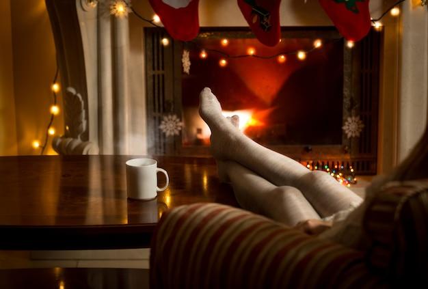 Belle gambe femminili in calze di lana che si scaldano al camino
