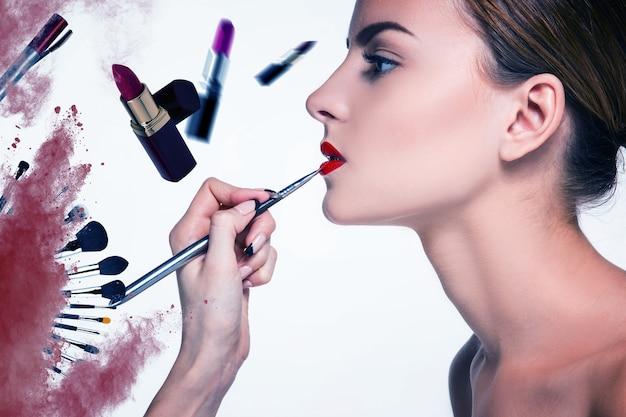 Belle labbra femminili con trucco e pennello su bianco. processo di lavoro del truccatore
