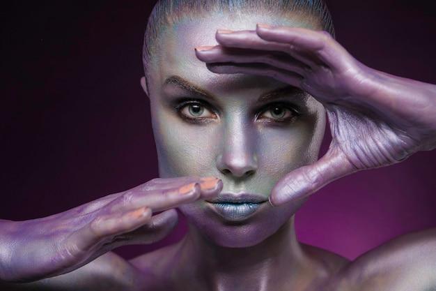 Bellissimo modello femminile con pera splendente body art colorato su viso e corpo