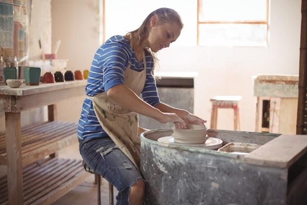 Bello vasaio femminile che fa vaso