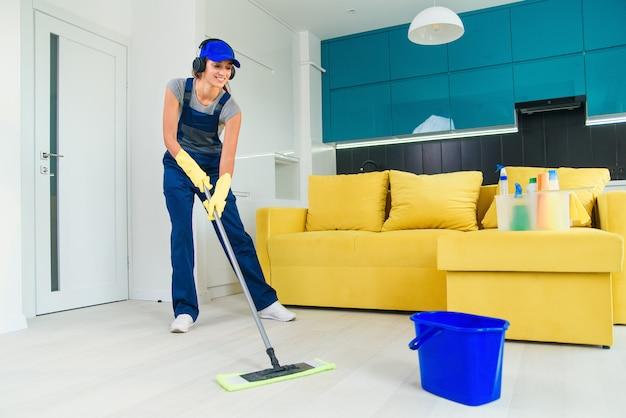 Bella donna detergente professionale in uniforme speciale con le cuffie che lava il pavimento con la scopa e ascolta la musica in appartamento. concetto di pulizie e pulizie.