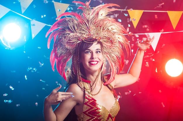 Bella ballerina di samba femminile che indossa il costume d'oro e sorridente
