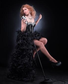 Bella cantante femminile in abito da concerto nero che esegue jazz. isolato su un buio