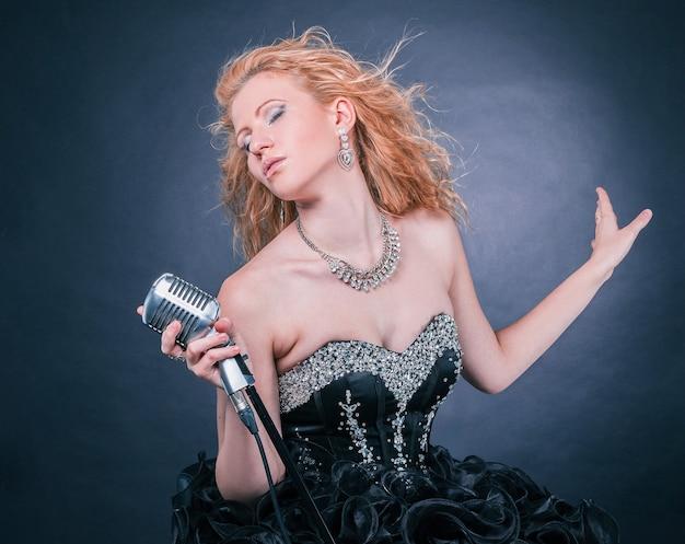 Bella cantante femminile in abito da concerto nero che esegue una composizione musicale. isolato su un buio